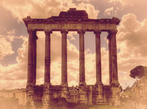 The ruins of the temple of Saturn in the Roman Forum in Rome, Italy. Retro toned Royalty Free Stock Photography