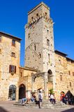 Piazza della Cisterna - San Gimignano. Tourists on the steps of the Cistern in front of Torre del Diavolo, one of the remaining 15 towers - San Gimignano Stock Images
