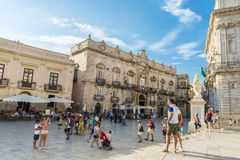 Piazza Duomo in Siracusa in Sicily, Italy. Siracusa, Italy - August 17, 2017: Piazza Duomo and the cathedral with people around in the old town of the historic royalty free stock photography