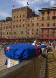 Piazza il campo in the morning. Colored flag of the contrada of Nicchio wrap a column up meaning that this space of the square is occupied, early in the morning Royalty Free Stock Image