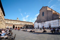 Piazza Maggiore, with views of the San Petronio church. Bologna, Italy - April 17 2017: Citizens and tourists, on a sunny day, walk and relax in Piazza Maggiore Royalty Free Stock Images