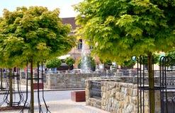 Piazza piacevole con molti alberi verdi durante il giorno di estate caldo Fotografia Stock