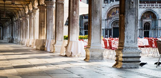 Piazza San Marco loggia with cafe tables. Early morning Venice scene with light coming through the receding pillars of the loggia of Piazza San Marco, St Marks Royalty Free Stock Photos