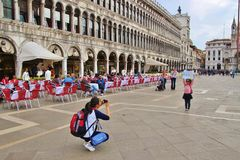 Piazza San Marco, Venice, Europe. Venice, Italy - April 4, 2017: On piazza San Marco. A tourist is photographing her little daughter holding up a city map of Royalty Free Stock Photos