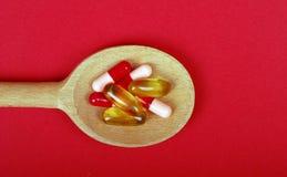 Comprimido e cápsulas de Omega 3 na colher de madeira Imagem de Stock Royalty Free