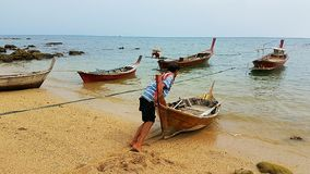 Fisherman going out to the sea. PIC shows longtailboat on the Andaman sea - colours blue red brown green. Cloudy scenery for postcards or background Royalty Free Stock Image