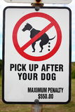 Sign-board Pick up after your dog. Sign-board in a park: PIC UP AFTER YOUR DOG - maximum penalty Australian $ 550.00 royalty free stock photo