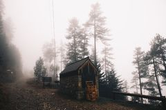 House in the foggy forest in a winter mountain royalty free stock images