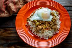 Picadillo a Cuban dish made of ground beef served on a bed of rice with a sunny side up egg on a red plate on a wooden kitchen tab stock photo