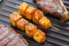Picanha steak with pineapple. Brazilian picanha steaks and pineapple skewers on grill Stock Photos