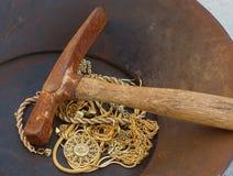 Picareta velha da mineração sobre a sucata do ouro em goldpan fotos de stock