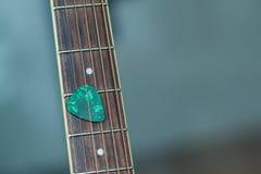 Picareta verde colorida da guitarra na placa do dedo Imagem de Stock