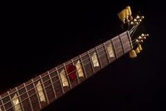 Picareta vermelha da guitarra no fingerboard e na obscuridade foto de stock royalty free
