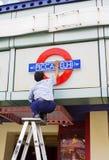 Delhi, India, Piccadelhi restaurant. An Indian man positions a sign on his restaurant in Delhi, India Stock Images