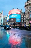 Piccadilly Circus neon signage reflected on street with taxy Stock Image