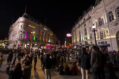 Piccadilly circus at night. People gathered around the square to enjoy the busy night life of the area. A lot of tourists taking selfies and admiring the buzz of royalty free stock photography