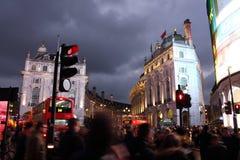 Piccadilly cirkus, London - - Februari 14th av 2015: Massor av människor bilar och typiska röda bussar som korsar gatorna i denna Fotografering för Bildbyråer