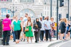Piccadillycircus met veel die mensen, toeristen en Londoners de verbinding kruisen Londen, het UK Stock Afbeelding