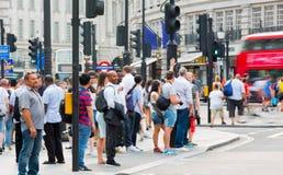 Piccadillycircus met veel die mensen, toeristen en Londoners de verbinding kruisen Londen, het UK Stock Afbeeldingen