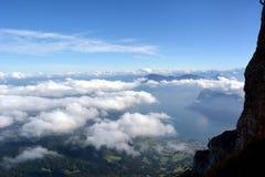 Picchi che si elevano sopra le nuvole Immagine Stock