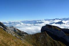 Picchi che si elevano sopra le nuvole Immagini Stock