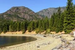 Picchi del granito sopra un lago calmo Immagini Stock