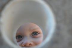 Picchi del ragazzo attraverso il foro Fotografia Stock Libera da Diritti