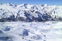 Picchi della neve delle alpi, valle con le piste dello sci nella località di soggiorno francese Immagine Stock Libera da Diritti