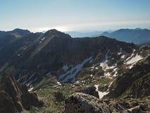 Picchi di alta montagna di estate con i punti della neve e del cielo blu Fotografia Stock