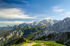 Picchi di alte montagne di luce solare delle alpi con il cielo blu della valle verde Fotografia Stock