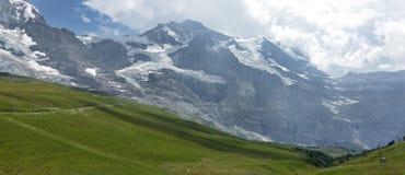 Picchi di Jungfrau e di Monch delle alpi svizzere sul modo a Kleine Scheidegg Fotografia Stock