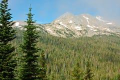 Picchi di montagna attraverso le nubi Wispy fotografia stock