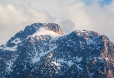 Picchi di montagna di Snowy al tramonto in primavera Immagine Stock Libera da Diritti