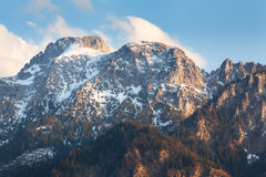 Picchi di montagna di Snowy al tramonto in primavera Immagini Stock Libere da Diritti