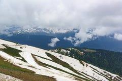 Picchi di montagna innevati nelle nuvole e nel pendio di collina, forniti di cabine di funivia nella priorità alta Immagini Stock