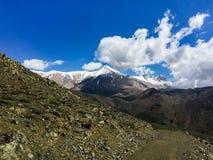 Picchi di montagna innevati sull'orizzonte nelle nuvole fotografia stock