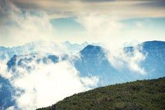Picchi di montagna nella mattina nebbiosa Fotografia Stock