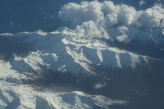 Picchi di montagna nevosi idilliaci sotto le nuvole dall'aereo Fotografie Stock Libere da Diritti
