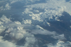 Picchi di montagna nevosi idilliaci sotto le nuvole dall'aereo Immagine Stock Libera da Diritti