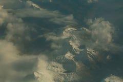 Picchi di montagna nevosi idilliaci sotto le nuvole dall'aereo Immagine Stock