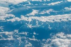 Picchi di montagna nevosi idilliaci sotto le nuvole dall'aereo Immagini Stock