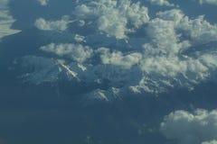 Picchi di montagna nevosi idilliaci sotto le nuvole dall'aereo Fotografia Stock Libera da Diritti