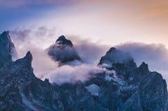 Picchi di montagna nuvolosi al tramonto Immagini Stock