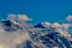 Picchi di montagna sopra le nuvole con neve Fotografia Stock