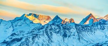 Picchi di montagne con neve al tramonto Fotografia Stock