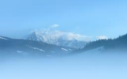 Picchi di Snowy alla mattina nebbiosa Fotografia Stock Libera da Diritti