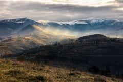 Picchi di Snowy sopra i pendii di collina in nebbia Immagini Stock Libere da Diritti