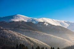 Picchi di Snowy sopra i pendii di collina in nebbia Fotografia Stock