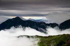 Picchi di Two-thousander delle alpi di Carnic nelle nuvole in Italia Fotografie Stock Libere da Diritti