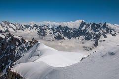 Picchi e alpinisti di Snowy in un giorno soleggiato, osservato da Aiguille du Midi, vicino a Chamonix-Mont-Blanc Immagine Stock